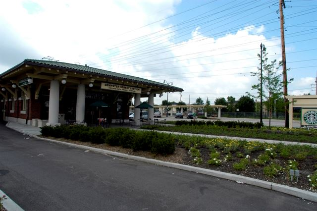 Image of train station building, with roadway, and a Starbucks coffee sign