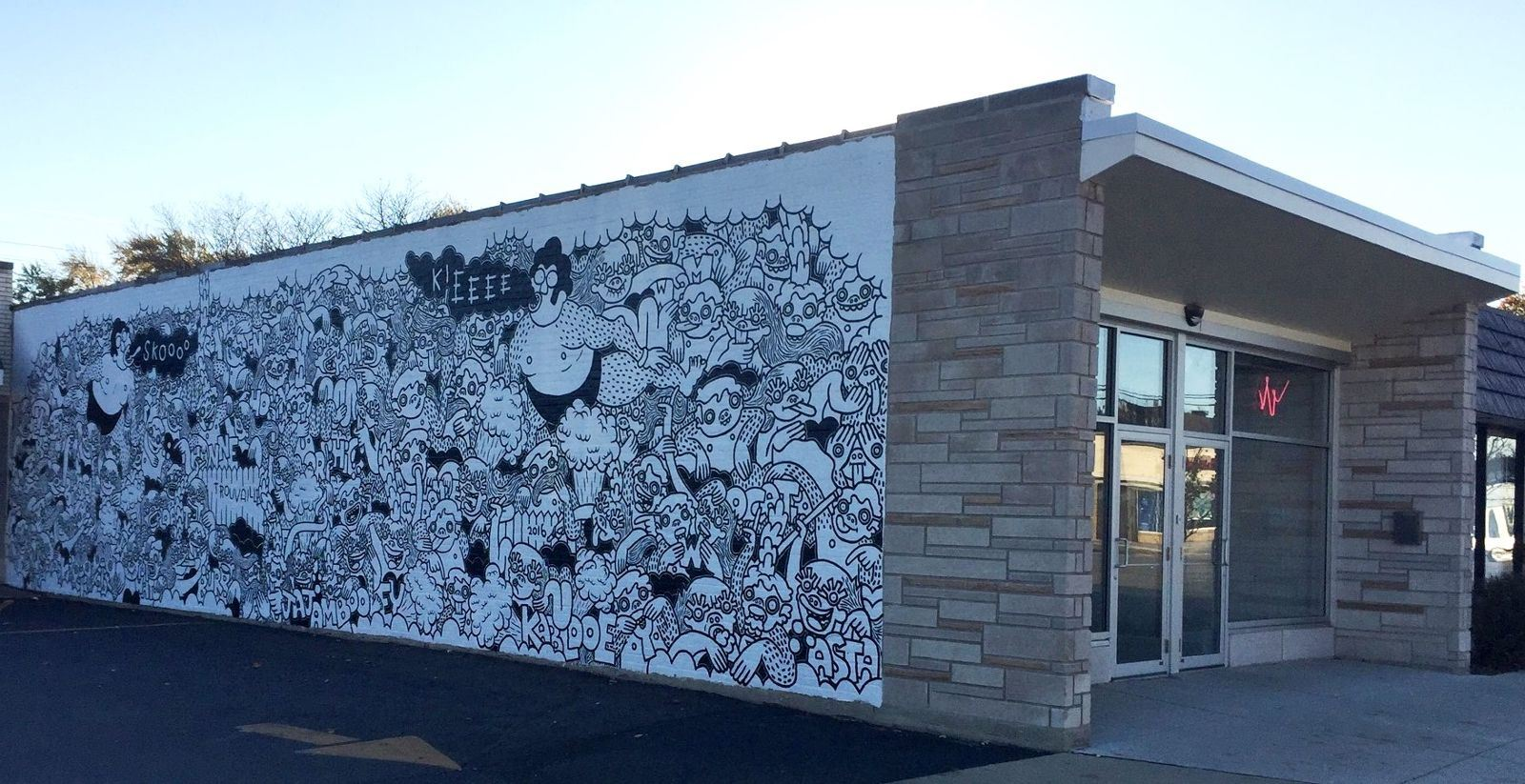 Image of building side, with black and white doodle-like art painted
