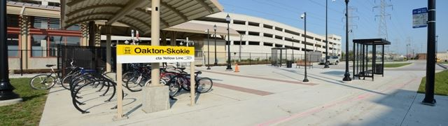 Image of front of train station, with bikes in a bike rack and sign with text Oakton Station